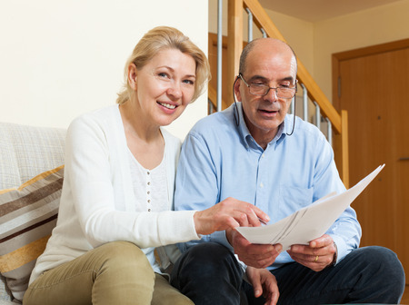 parsimony: Senior mature couple with financial documents on sofa in home Stock Photo