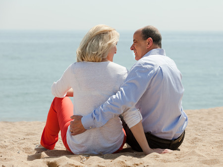 Rear view of senior man and mature woman together against sea in summer photo