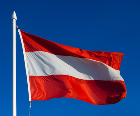 Flag of Austria against blue sky during wind photo