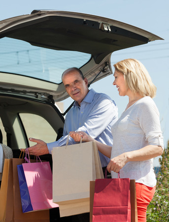 novelties: Happy mature husband and wife putting in the cars trunk  shopping bags