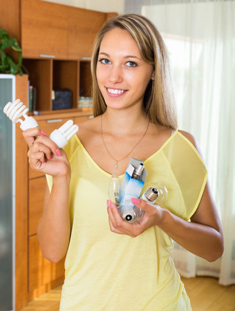Young smiling woman holding light bulbs at home photo