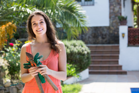 pruning scissors: Smiling long-haired woman working with pruning scissors Stock Photo
