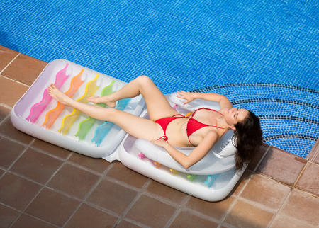 a bathing place: Young woman in bikini relaxing on inflatable mattress near pool