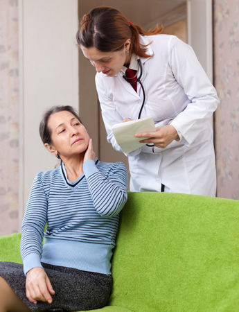 50 to 60 years: doctor asks sick mature patient feels at medical hospital Stock Photo