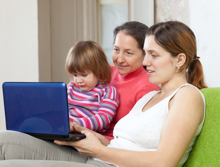 Family of three generations with netbook on sofa in living room photo