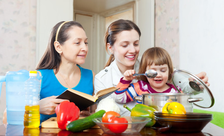Happy family together cook with cookbook in the kitchen at home photo