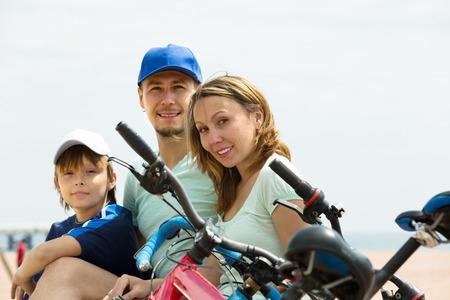 ciclos: Familia de tres con ciclos detr�s de mar en d�a de verano Foto de archivo