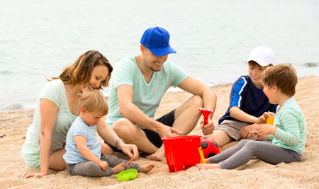 Parents talking and kids playing with sand at sea shore photo