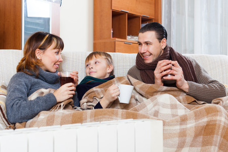 parents and teenage son warming near warm heater in home Stock Photo