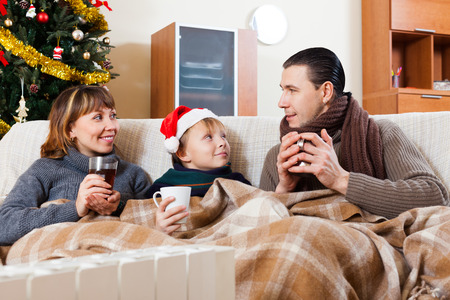 Happy parents and teenage son with cups of tea warming near warm calorifer in Christmas time