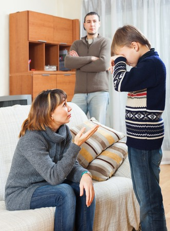 Serious parents with crying son in home interior photo