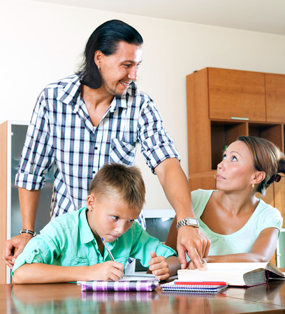 10 12: Happy parents helping to son with homework in home interior