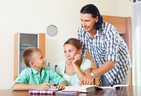 Smiling couple with teenager son doing homework in home interior photo