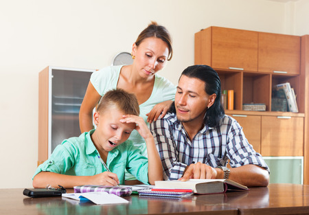 Teenager schoolboy and parents studying together in home photo