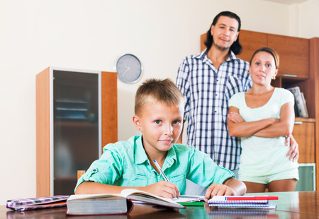 Smiling couple watching on teenager son doing homework in home interior photo