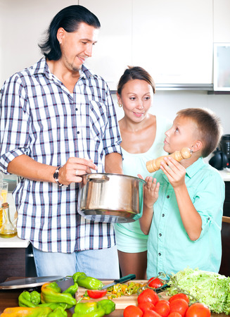 10 12: Happy man and woman with boy adding spices or salt to the pot and in home kitchen