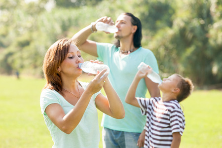 ordinary family of three drinking water from plastic bottles in summer park photo
