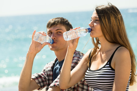 man drinking water: Thirsty young couple enjoying bottle of water at seashore in sunny day
