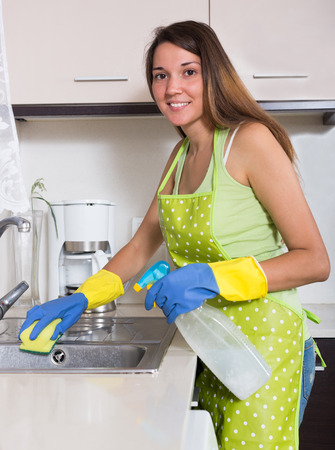 Happy young woman working  in kitchen at home photo