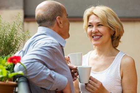 Positive  mature couple having morning coffee at balcony photo