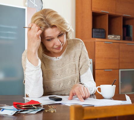 parsimony: Serious blonde woman thinking about the financial issue at  home Stock Photo
