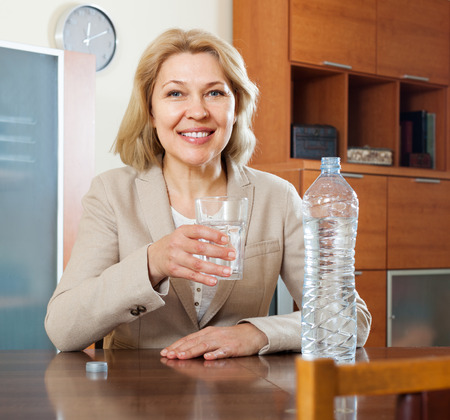 Smiling mature woman drinking water from glass photo