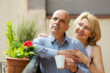 Happy elderly  couple having morning coffee at balcony and smiling photo