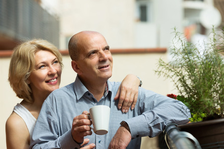 Smiling senior couple discussing and drinking coffee at balcony photo