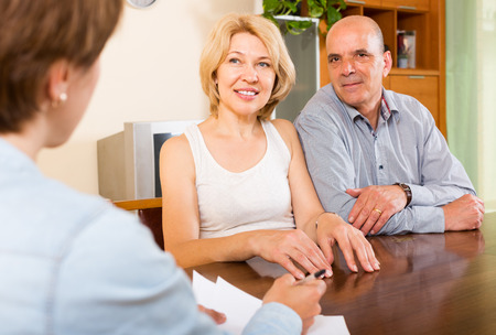 Smiling mature couple  talking with employee at office photo