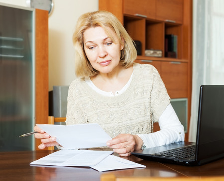60 something: Working woman with notebook and financial documents at table in office Stock Photo