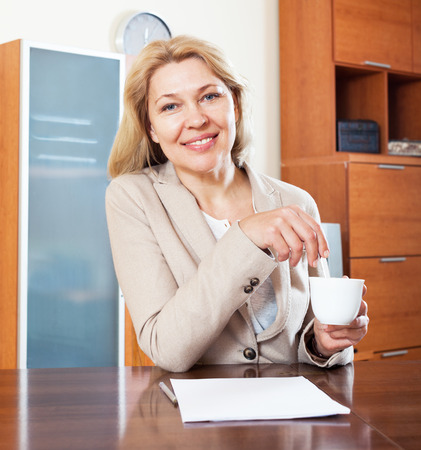 fifty something: smiling  woman sitting at a table in the office   with paperwork