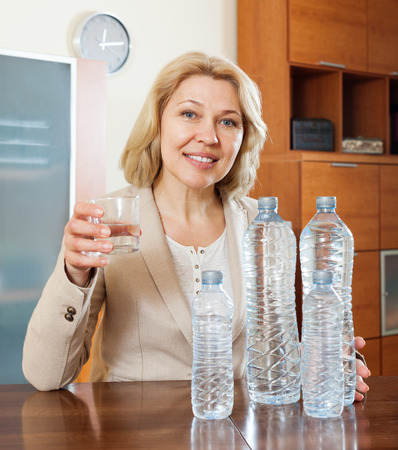 Cherful ordinary mature woman drinking water at home photo