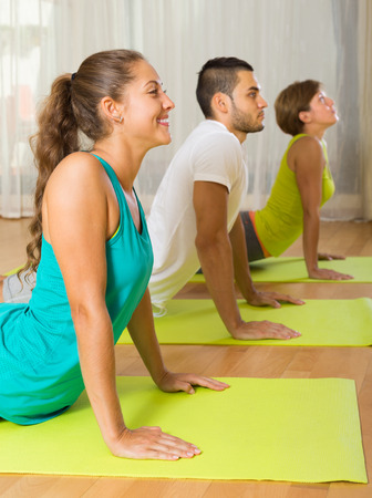 Group of adult people having yoga class in sport club photo