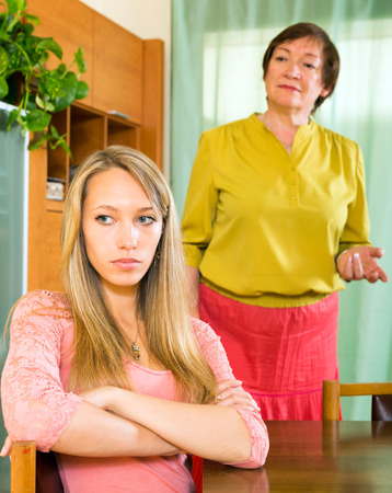 squabble: Sad adult daughter at table against mature mother after conflict