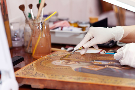 Art restorer working on the ancient Christian icon with spatula at restoration workshop photo