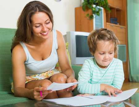 Cheerful woman and daughter signing application form for kindergarten indoor