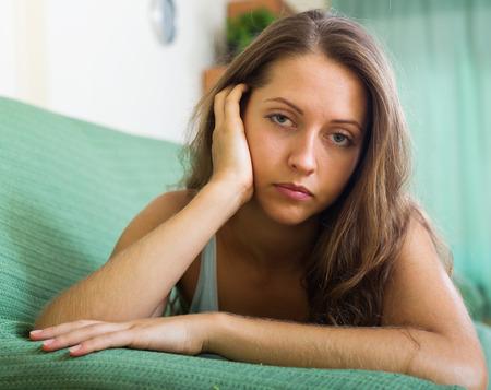 soltería: Mujer solitaria en el sofá en casa