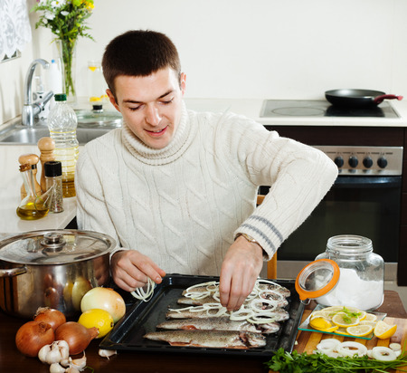 man cooking raw fish and onion in baking sheet at home kitchen