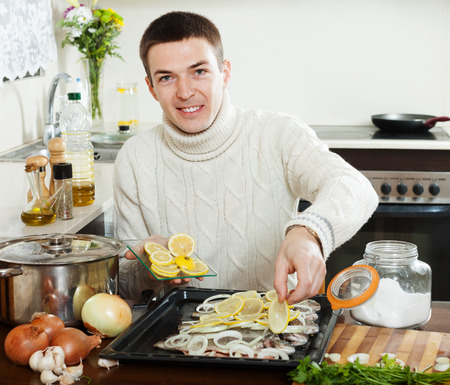 roasting pan: Handsome man with raw fish on roasting pan at home