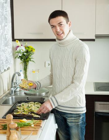 roasting pan: Smiling guy cooking  fish with lemon in roasting pan at  kitchen