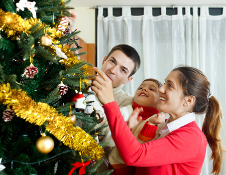 family of three preparing for Christmas at home photo