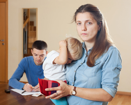 covetous: Family of three with baby having quarrel over money Stock Photo