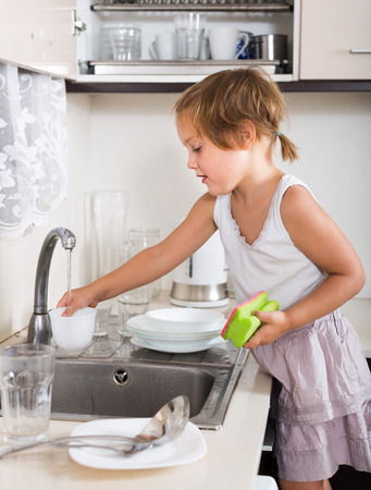 Small child cleaning dishes in the kitchen photo