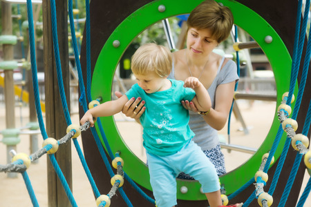 dexterity: Baby girl with mother developing dexterity at playground Stock Photo