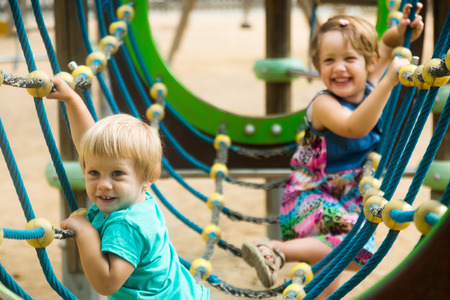 deftness: little sisters at action-oriented playground in summer park