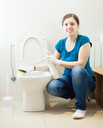 Smiling  woman cleaning toilet bowl with sponge and cleaner at her home photo
