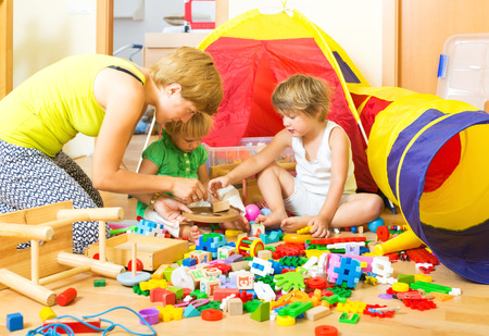 Mother and children playing with  toys in  interior photo