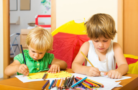 2 3 years: Siblings sketching with paper and pencils in home interior