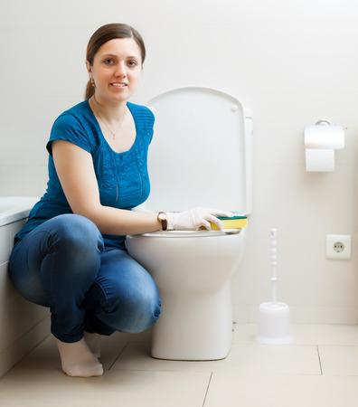 Smiling girl in blue cleaning toilet bowl photo