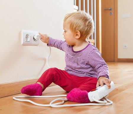 Kleinkind spielt mit Verlängerungskabel und Steckdose zu Hause Standard-Bild